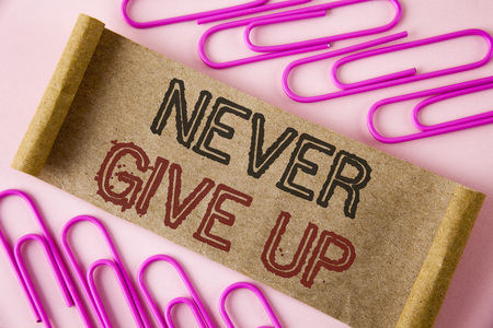 Handwriting text writing Never Give Up. Concept meaning Be persistent motivate yourself succeed never look back written Folded Cardboard paper piece plain background within Paper Pins.