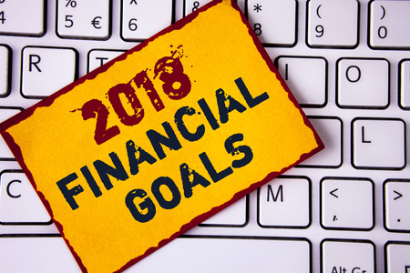 Handwriting text writing 2018 Financial Goals. Concept meaning New business strategy earn more profits less investment written Sticky note paper placed White Keyboard. Top view.