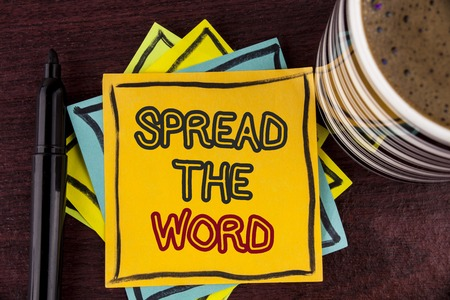 Writing note showing  Spread The Word. Business photo showcasing Run advertisements to increase store sales many fold written Sticky Note paper Wooden background Coffee Cup and Marker Foto de archivo