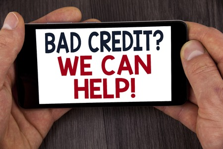 Writing note showing  Bad Credit Question We Can Help Motivational Call. Business photo showcasing achieve good debt health written Mobile Phone Screen holding by man the wooden background. Stock Photo
