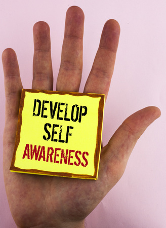 Text sign showing Develop Self Awareness. Conceptual photo What you think you become motivate and grow written Yellow Sticky Note Paper placed the Hand the plain background. Foto de archivo