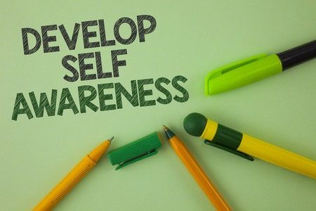 Handwriting text writing Develop Self Awareness. Concept meaning What you think you become motivate and grow written Plain Green background Pens next to it. Foto de archivo