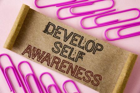 Handwriting text writing Develop Self Awareness. Concept meaning What you think you become motivate and grow written Folded Cardboard paper piece plain background within Paper Pins.
