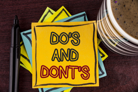 Writing note showing  DoS And DonTs. Business photo showcasing What can be done and what cannot be knowing right wrong written Sticky Note paper Wooden background Coffee Cup and Marker