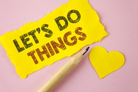 Writing note showing  Let Us Do Things. Business photo showcasing Try something new find happiness mastering it by practice written Tear Yellow paper piece Pink background Heart next to it. Stock Photo