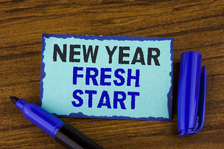 Text sign showing New Year Fresh Start. Conceptual photo Time to follow resolutions reach out dream job written Sticky Note paper the wooden background Marker next to it. Stock Photo