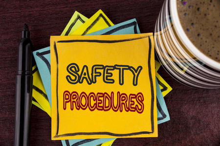 Writing note showing  Safety Procedures. Business photo showcasing Follow rules and regulations for workplace security written Sticky Note paper Wooden background Coffee Cup and Marker