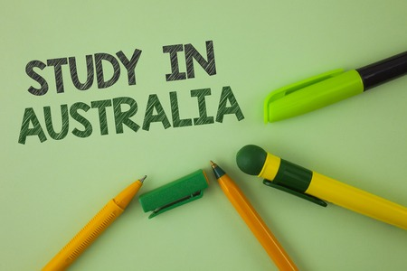 Handwriting text writing Study In Australia. Concept meaning Graduate from oversea universities great opportunity written Plain Green background Pens next to it.