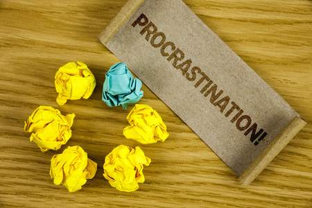 Text sign showing Procrastination Motivational Call. Conceptual photo Delay or Postpone something boring written Folded Cardboard Paper piece wooden background Crumpled Paper Balls.