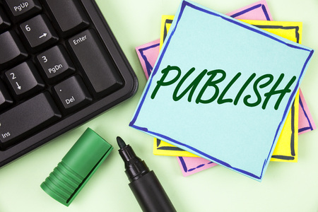 Handwriting text writing Publish. Concept meaning Make information available to people Issue a written product written Sticky Note paper plain Green background Marker and Keyboard. Stock Photo