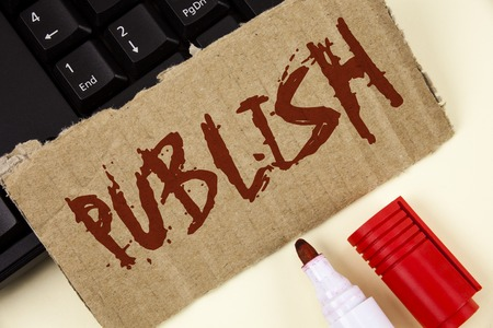 Text sign showing Publish. Conceptual photo Make information available to people Issue a written product written Tear Cardboard Piece plain background Keyboard and Marker next to it.