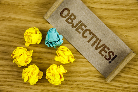 Text sign showing Objectives Motivational Call. Conceptual photo Goals planned to be achieved Desired targets written Folded Cardboard Paper piece wooden background Crumpled Paper Balls.