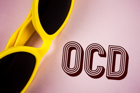 Text sign showing Ocd. Conceptual photo Obsessive Compulsive Disorder Psychological Illness Medical Condition written Plain Pink background Sunglasses next to it.