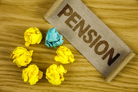 Text sign showing Pension. Conceptual photo Income seniors earn after retirement Saves for elderly years written Folded Cardboard Paper piece wooden background Crumpled Paper Balls. Reklamní fotografie