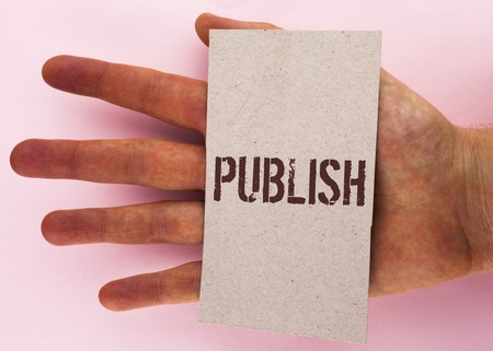 Text sign showing Publish. Conceptual photo Make information available to people Issue a written product written Cardboard Piece placed Hand the plain background. Stock Photo
