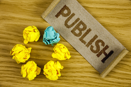 Text sign showing Publish. Conceptual photo Make information available to people Issue a written product written Folded Cardboard Paper piece wooden background Crumpled Paper Balls.