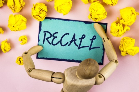 Handwriting text writing Recall. Concept meaning Bring back to memory Ordering the return of a person or product written Sticky note paper within Paper Balls plain background Wooden Toy