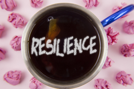 Conceptual hand writing showing Resilience. Business photo showcasing Capacity to recover quickly from difficulties Persistence written Tea in Cup within Paper Balls plain background.
