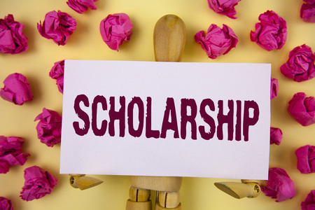 Text sign showing Scholarship. Conceptual photo Grant or Payment made to support education Academic Study written Sticky Note paper plain background Paper Balls and Wooden Robot Toy.
