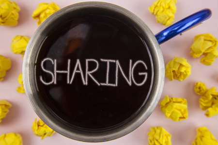 Writing note showing  Sharing. Business photo showcasing To Share Give a portion of something to another Possess in common written Black Tea in Cup within Paper Balls plain background. Stock Photo