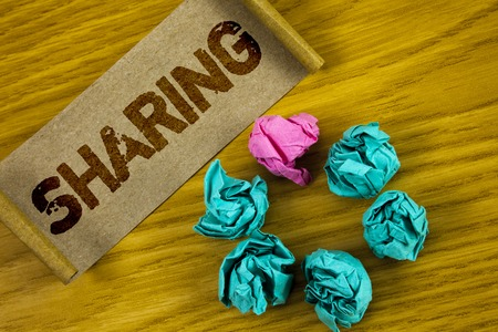 Handwriting text writing Sharing. Concept meaning To Share Give a portion of something to another Possess in common written Folded Cardboard Paper piece wooden background Paper Balls.