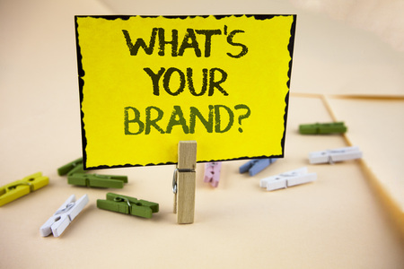Writing note showing  What Is Your Brand Question. Business photo showcasing Define Individual trademark Identify Company written Yellow Sticky Note Paper on plain background Wooden Clips.