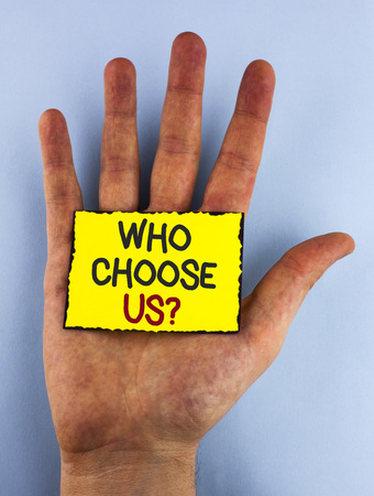 Text sign showing Who Choose Us Question. Conceptual photo Kind of people that select our Services or Products written Yellow Sticky Note placed the Hand plain background. 写真素材
