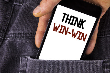 Conceptual hand writing showing Think Win-Win. Business photo text Negotiation strategy for both partners to obtain benefits written Mobile Phone holding by man the Jeans background. Фото со стока