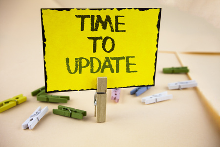 Writing note showing  Time To Update. Business photo showcasing Renewal Updating Changes needed Renovation Modernization written Yellow Sticky Note Paper on plain background Wooden Clips.