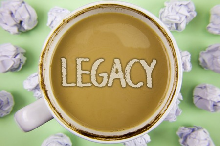 Handwriting text Legacy. Concept meaning Transmitted Received from an ancestor Money Properties given by will written Tea in White Cup within Crumpled Paper Balls plain Green background. Stock Photo