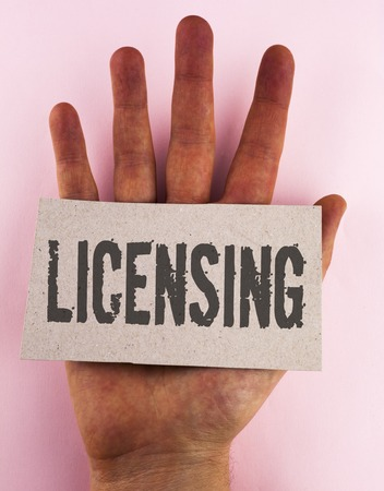 Conceptual hand writing showing Licensing. Business photo text Grant a license Legally permit the use of something Allow activity written Cardboard Piece placed the Hand plain background.