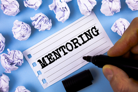 Mentoring. Business concept for To give advice or support to a younger less experienced person written by Man Notepad paper plain blue background Paper Balls next to it. Stockfoto