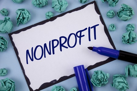 Writing note showing  Nonprofit. Business photo showcasing Activities that do not generate revenues to the executor written Sticky note paper within Paper Balls plain background Pen Фото со стока