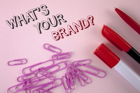 Writing note showing  What Is Your Brand Question. Business photo showcasing Define Individual trademark Identify Company written plain Pink background Pen Marker and Paper Pins next to it.