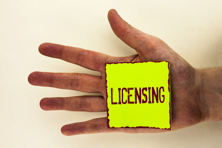 Word writing text Licensing. Business concept for Grant a license Legally permit the use of something Allow activity written Sticky Note Paper placed the Hand the plain background.