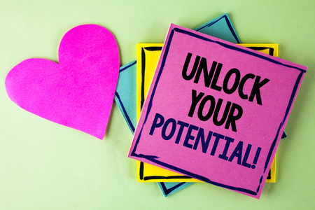 Writing note showing  Unlock Your Potential Motivational Call. Business photo showcasing Reveal talent Sow Skills Abilities written Pink Sticky Note Paper plain background Heart next to it. Stock Photo