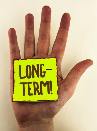 Handwriting text writing Long-Term Motivational Call. Concept meaning Occurring over large period of time Future plans written Sticky Note Paper placed Hand the plain background. Reklamní fotografie