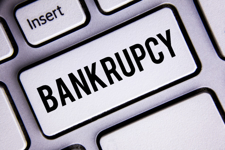 Text sign showing Bankrupcy. Conceptual photo Company under financial crisis goes bankrupt with declining sales written White Keyboard Key with copy space. Top view. Stock Photo