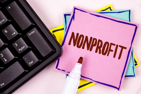 Text sign showing Nonprofit. Conceptual photo Activities that do not generate revenues to the executor written Pink Sticky Note paper plain background Marker and Black Keyboard. Фото со стока