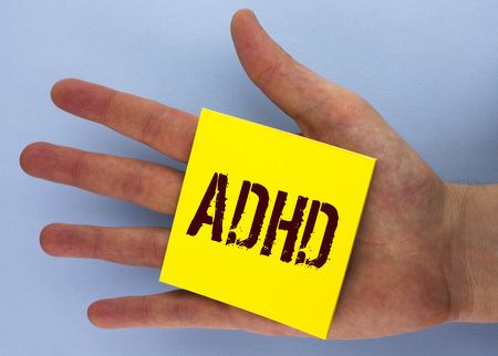 Text sign showing Adhd. Conceptual photo Learning made easier for children teaching no more a difficult task written Yellow Sticky Note Paper placed  Hand the plain background.