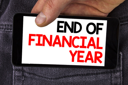 Writing note showing  End Of Financial Year. Business photo showcasing Taxes time accounting June database cost Sheets written Mobile Phone Screen holding by man the Jeans background.