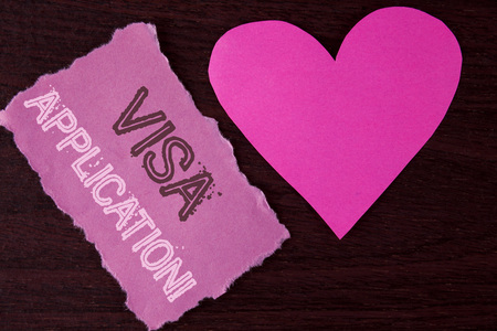 Handwriting text writing Visa Application Motivational Call. Concept meaning sheet to provide your basic information written Tear Sticky Note Paper Piece wooden background Heart next to it. Foto de archivo