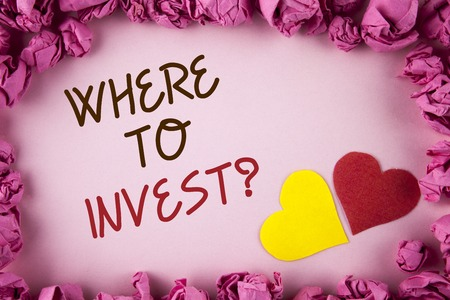 Word writing text Where To Invest Question. Business concept for Right Place Stock Share to spend your savings in written plain background within Pink Paper Balls Hearts next to it. Stock Photo