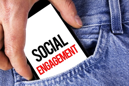 Conceptual hand writing showing Social Engagement. Business photo showcasing post gets high reach Likes Ads SEO Advertising Marketing written Mobile phone holding by man the Jeans background.