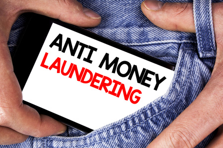 Handwriting text writing Anti Monay Laundring. Concept meaning entering projects to get away dirty money and clean it written Mobile phone screen holding by man the jeans background.