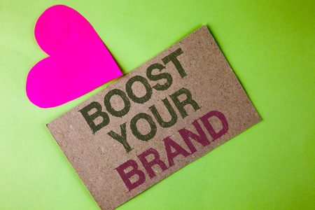 Conceptual hand writing showing Boost Your Brand. Business photo text improve your models name in your field overcome competitors written Cardboard Piece the plain background Heart next to it Stock Photo