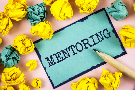 Text sign showing Mentoring. Conceptual photo To give advice or support to a younger less experienced person written Sticky Note paper within Paper Balls plain background Pencil. Stockfoto