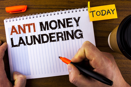 Text sign showing Anti Monay Laundring. Conceptual photo entering projects to get away dirty money and clean it written by Man Notepad holding Marker Wooden background Today Cup and Clip.