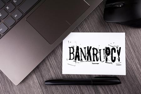バンクルプシーを示すメモを書く。金融危機の下で会社を紹介するビジネス写真は、木製の背景ラップトップマウスペンを書いた付箋紙の売り上げの減少で倒産します 写真素材 - 99849876