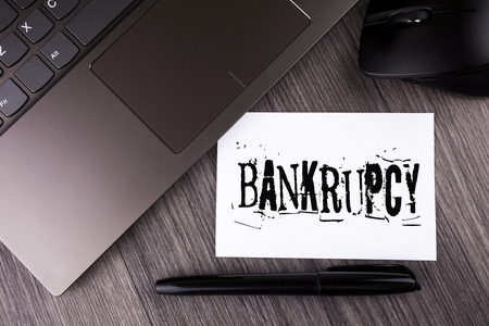 Writing note showing  Bankrupcy. Business photo showcasing Company under financial crisis goes bankrupt with declining sales written Sticky Note Paper the wooden background Laptop Mouse Pen Фото со стока